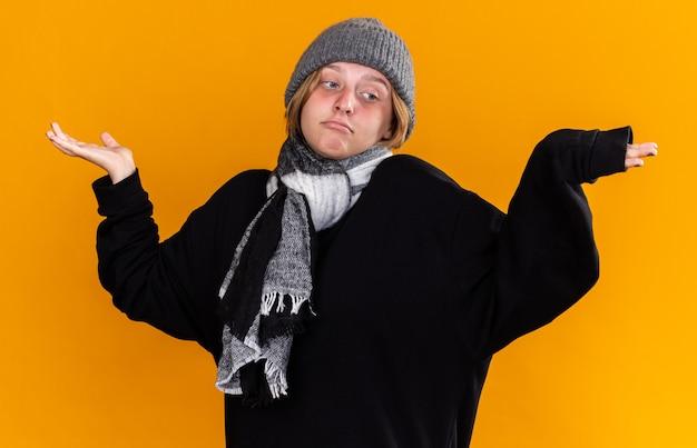 Нездоровая молодая женщина в теплой шляпе и с шарфом на шее чувствует себя больной, страдает от простуды и гриппа, выглядит смущенной, пожимая плечами