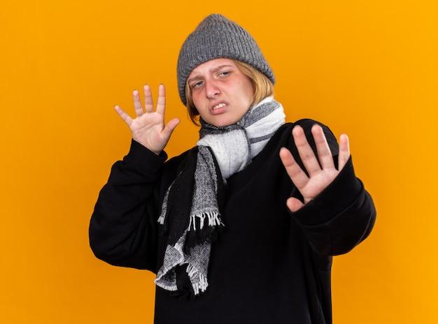 건강에 해로운 젊은 여성이 따뜻한 모자를 쓰고 그녀의 목 주위에 스카프가 감기와 독감으로 고통받는 고통을 느끼며 손으로 주황색 벽 위에 서서 방어 제스처를 만듭니다.