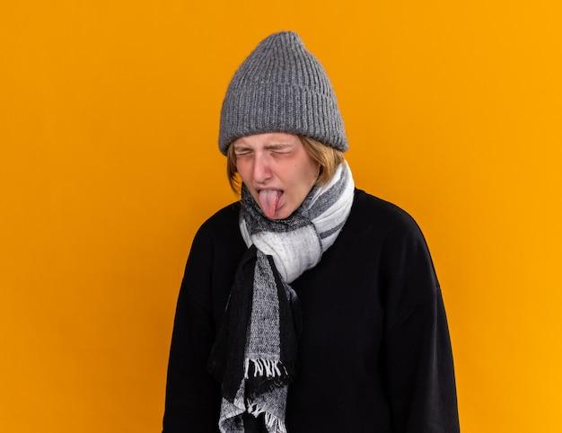 따뜻한 모자를 쓰고 목에 스카프를 낀 건강에 해로운 젊은 여성이 혐오스러운 표정으로 혀를 튀어 나와 감기와 독감으로 고통받습니다.