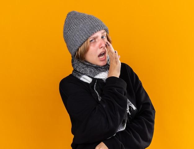暖かい帽子をかぶり、首にスカーフを巻いて風邪やインフルエンザに苦しんでいる不健康な若い女性が、オレンジ色の壁の上に立って口の近くに手を置いて秘密を話す