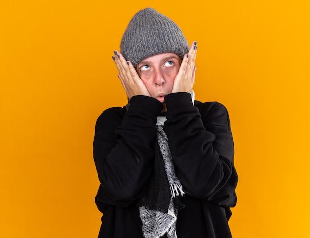 暖かい帽子をかぶり、首にスカーフを巻いて、風邪やインフルエンザに苦しんでいる不健康な若い女性が、オレンジ色の壁の上にイライラした表情で顔に触れている