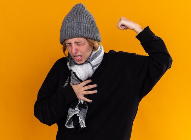 따뜻한 모자를 쓰고 목에 스카프가 달린 건강에 해로운 젊은 여성이 오렌지 벽 위에 서있는 독감 기침으로 고통받는 아픈 느낌
