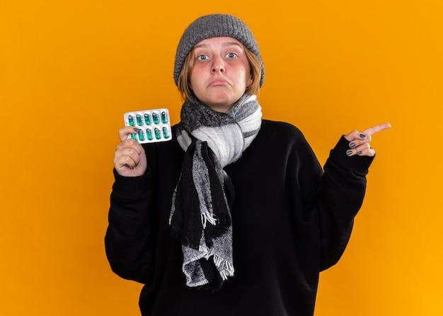 건강에 해로운 젊은 여성이 따뜻한 모자를 쓰고 그녀의 목 주위에 스카프를 낀 채로 독감으로 고통을 느끼고 오렌지 벽 위에 서있는 쪽을 손가락으로 가리키는 혼란스러워 보이는 약을 들고 있습니다.