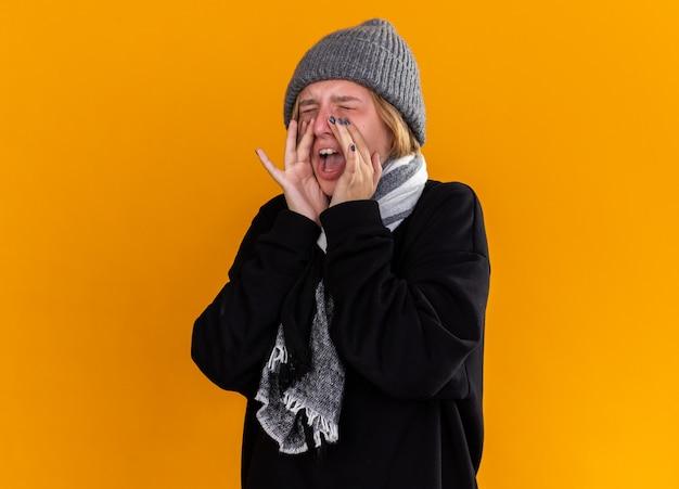 따뜻한 모자를 쓰고 건강에 해로운 젊은 여성이 오렌지 벽 위에 서있는 입 근처의 손으로 독감으로 외치는 독감으로 고통받는 그녀의 목 주위에 스카프로