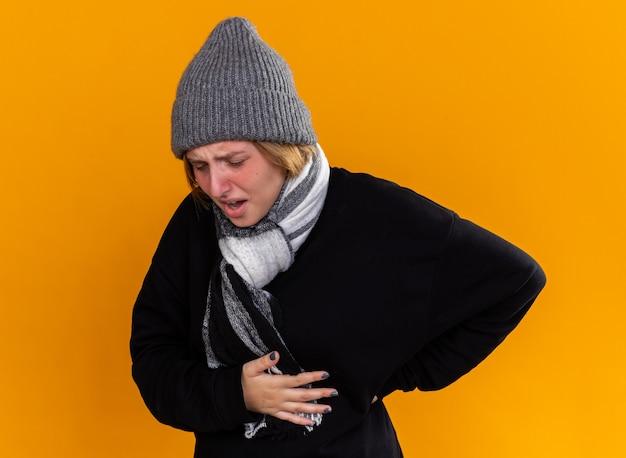 暖かい帽子をかぶり、首にスカーフを巻いた不健康な若い女性が、インフルエンザに苦しんで背中に触れ、オレンジ色の壁の上に立って痛みを感じている