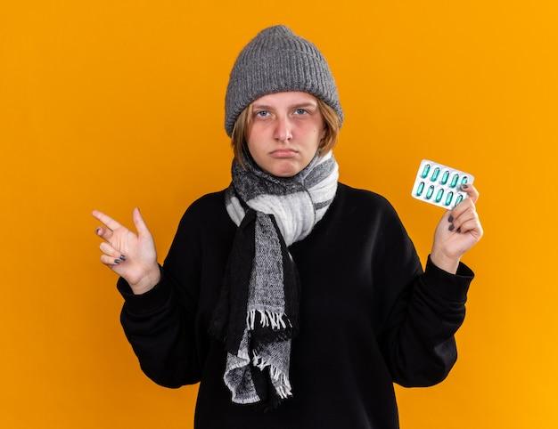 따뜻한 모자를 쓰고 건강에 해로운 젊은 여성이 심각한 얼굴로 감기와 독감으로 약을 들고 끔찍한 고통을 느끼는 그녀의 목 주위에 스카프