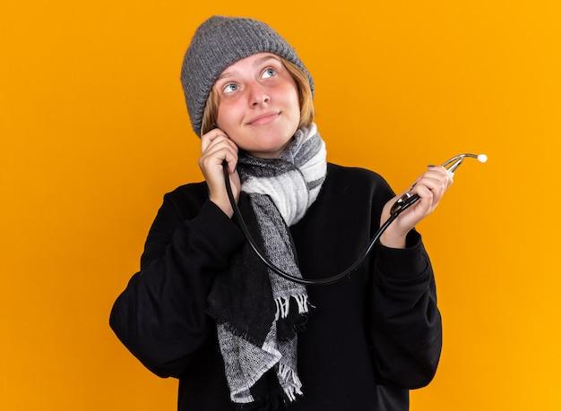 Нездоровая молодая женщина в теплой шляпе и с шарфом на шее, страдающая от простуды и гриппа, чувствует себя лучше, держа стетоскоп, глядя в сторону, улыбаясь, стоя у оранжевой стены