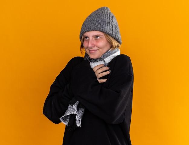 Giovane donna malsana che indossa un cappello caldo e con una sciarpa intorno al collo tosse freddo sentendosi meglio sorridere