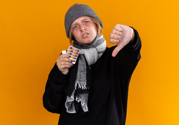 Giovane donna malsana che indossa un cappello caldo e con una sciarpa intorno al collo sentendosi malata soffre di raffreddore e influenza tenendo in mano una bottiglia di medicina che mostra il pollice verso