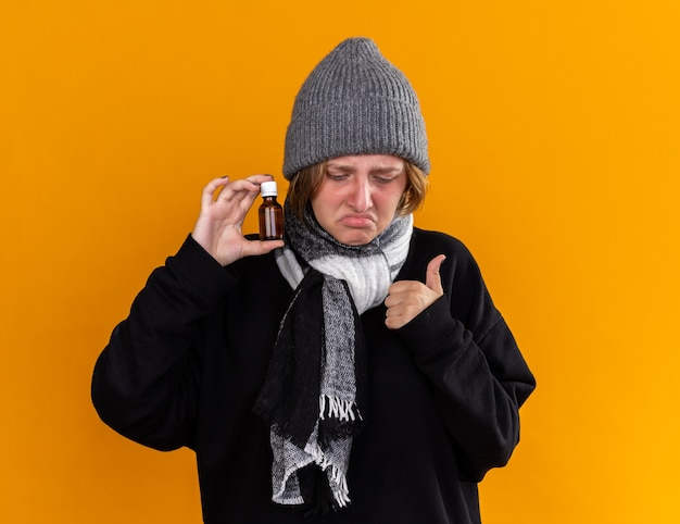 Giovane donna malsana che indossa un cappello caldo e con una sciarpa intorno al collo sentendosi malata soffre di raffreddore e influenza con in mano una bottiglia di medicina che mostra i pollici in su