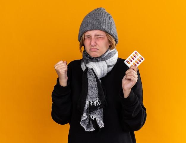 Giovane donna malsana che indossa un cappello caldo e con una sciarpa intorno al collo si sente male soffre di raffreddore e influenza tenendo pillole stringendo il pugno con espressione infastidita