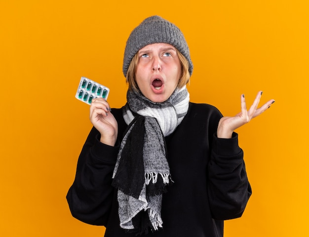 Unhealthy young woman wearing warm hat and with scarf around her neck feeling sick suffering from cold and flu holding pills shouting with disappointed expression standing over orange wall