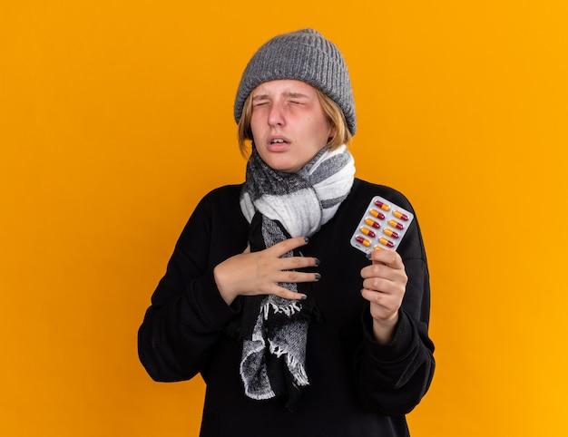 Giovane donna malsana che indossa un cappello caldo e con una sciarpa intorno al collo sentendosi malata soffre di raffreddore e influenza tenendo pillole in piedi sul muro arancione