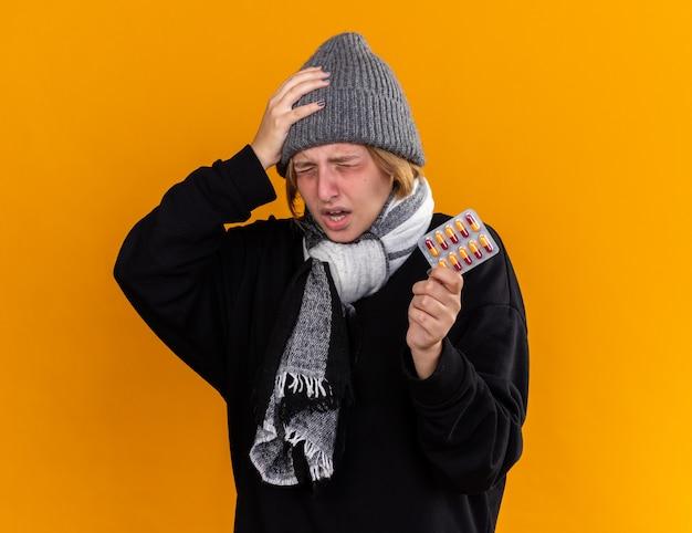 Giovane donna malsana che indossa un cappello caldo e con una sciarpa intorno al collo si sente male soffre di raffreddore e influenza tenendo pillole toccando la testa avendo la febbre