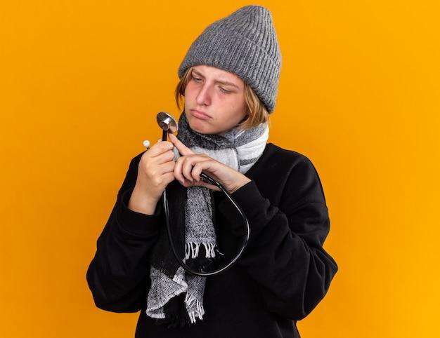 Giovane donna malsana che indossa un cappello caldo e con una sciarpa intorno al collo sentendosi malata soffre di raffreddore e influenza tenendo lo stetoscopio guardandolo con una faccia seria in piedi sul muro arancione