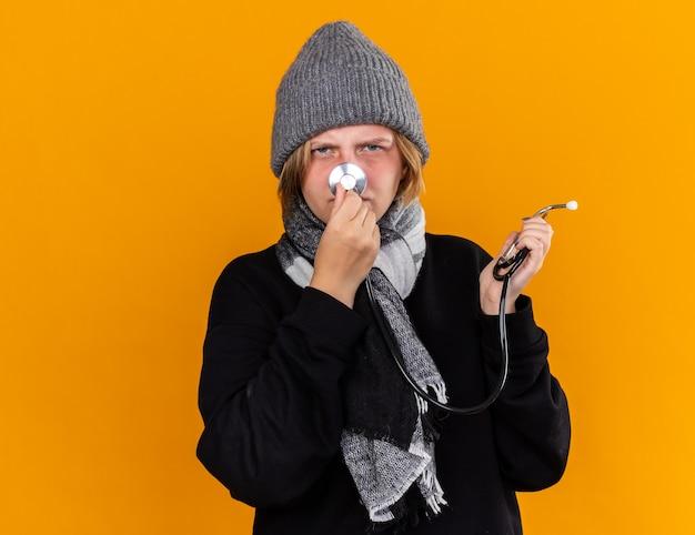 Giovane donna malsana che indossa un cappello caldo e con una sciarpa intorno al collo che si sente malata soffre di raffreddore e influenza tenendo lo stetoscopio