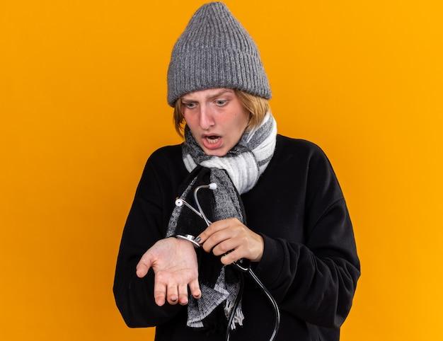 Giovane donna malsana che indossa un cappello caldo e con una sciarpa intorno al collo sentendosi male soffrendo di raffreddore e influenza ascoltando il suo polso usando lo stetoscopio