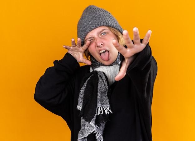 Giovane donna malsana che indossa un cappello caldo e con una sciarpa intorno al collo sentendosi malata soffre di raffreddore e influenza facendo gesti con le mani spaventose