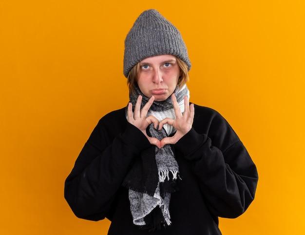 Giovane donna malsana che indossa un cappello caldo e con una sciarpa intorno al collo sentendosi malata soffre di raffreddore e influenza facendo il gesto del cuore con il dito con espressione triste in piedi sul muro arancione