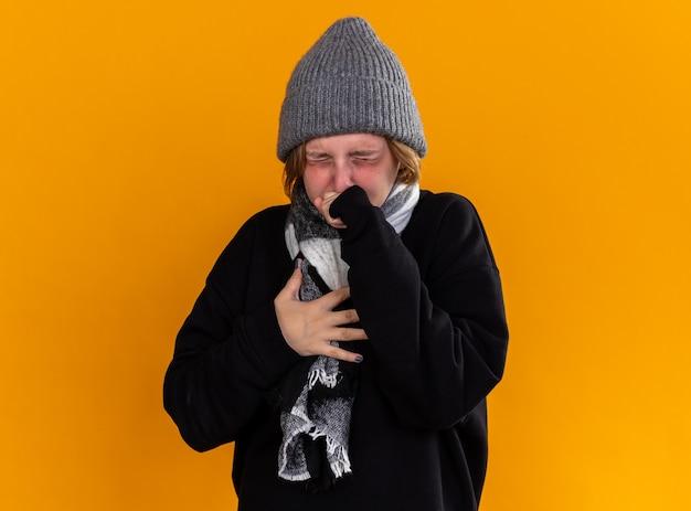 Giovane donna malsana che indossa un cappello caldo e con una sciarpa intorno al collo si sente male e soffre di influenza tosse e starnuti