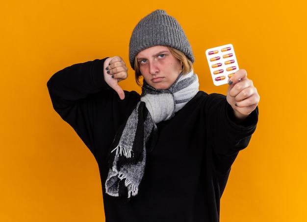 Giovane donna malsana che indossa un cappello caldo e con una sciarpa intorno al collo sentendosi malata soffre di influenza tenendo pillole che mostra i pollici verso il basso in piedi sul muro arancione