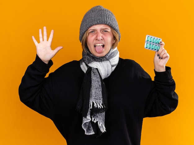 Unhealthy young woman wearing warm hat and with scarf around her neck feeling terrible suffering from cold and flu holding pills sticking out tongue with disgusted expression on orange wall