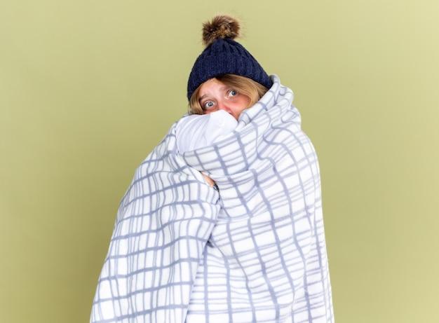 따뜻한 모자를 쓰고 건강에 해로운 젊은 여성이 담요를 들고 베개를 감싸고 녹색 벽 위에 감기 서서 고통받는 기분이 좋지 않습니다.