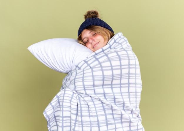 눈을 감고 웃고 베개를 들고 담요로 싸서 따뜻한 모자를 쓰고 건강에 해로운 젊은 여성이 녹색 벽 위에 서 자고 싶어합니다.
