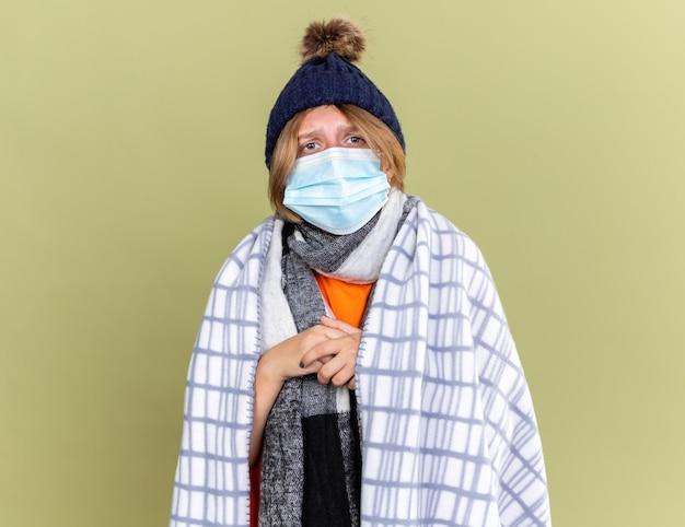暖かい帽子をかぶった不健康な若い女性が、顔の保護マスクで毛布を包み、インフルエンザと風邪に苦しんで緑の壁の上に立っている
