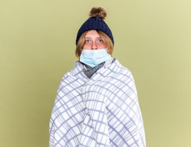緑の壁の上に立つインフルエンザに苦しんでいる顔の保護マスクで毛布で包まれた暖かい帽子をかぶった不健康な若い女性