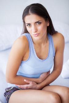 Unhealthy young woman with stomachache leaning on the bed at home
