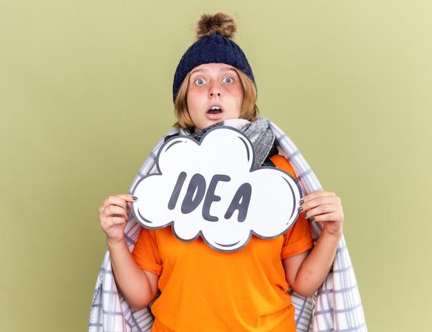 暖かい帽子とスカーフを首に巻いた不健康な若い女性が毛布に包まれ、体調が悪いと感じ、緑の壁の上に立って混乱しているように見える言葉のアイデアで吹き出し記号を保持