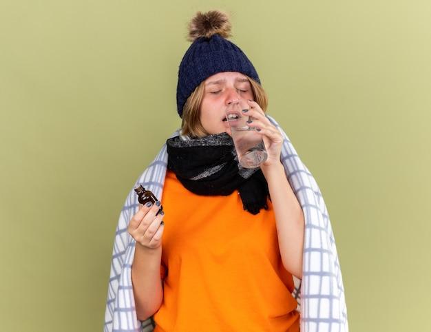 暖かい帽子と首にスカーフを巻いた不健康な若い女性が、インフルエンザの飲用薬に苦しんでいるコップ一杯の水に滴り落ちるのが気分が悪いと感じています。