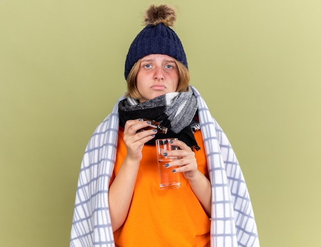 暖かい帽子とスカーフを首に巻いた不健康な若い女性が毛布に包まれ、緑の壁の上に立つインフルエンザに苦しむ水の入ったグラスに、体調が悪いと感じた滴が滴る