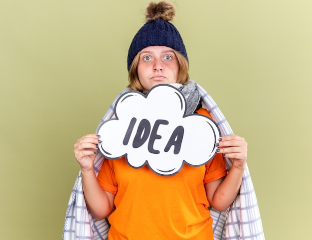 Unhealthy young woman with warm hat and scarf around neck wrapped in blanket feeling unwell caught cold holding speech bubble sign with word idea looking worried standing over green wall