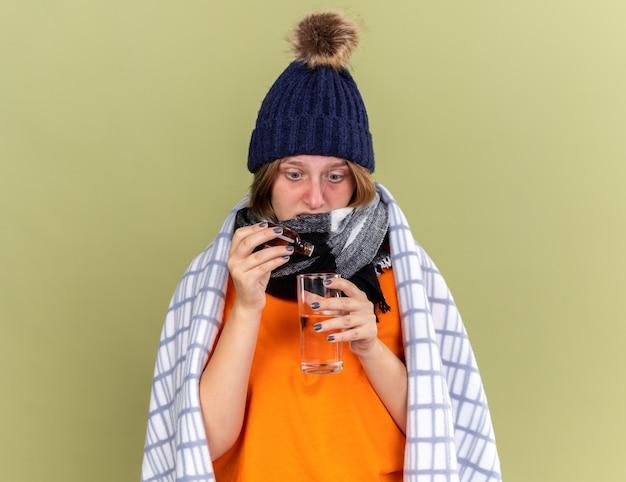 Giovane donna malsana con cappello caldo e sciarpa intorno al collo avvolta in una coperta sensazione di malessere gocce gocciolanti in un bicchiere d'acqua che soffre di influenza in piedi sul muro verde