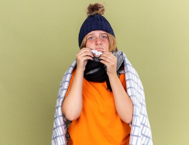 Giovane donna malsana con cappello caldo e sciarpa intorno al collo avvolta in una coperta sentirsi male con in mano una toppa che sembra confusa e preoccupata in piedi sul muro verde