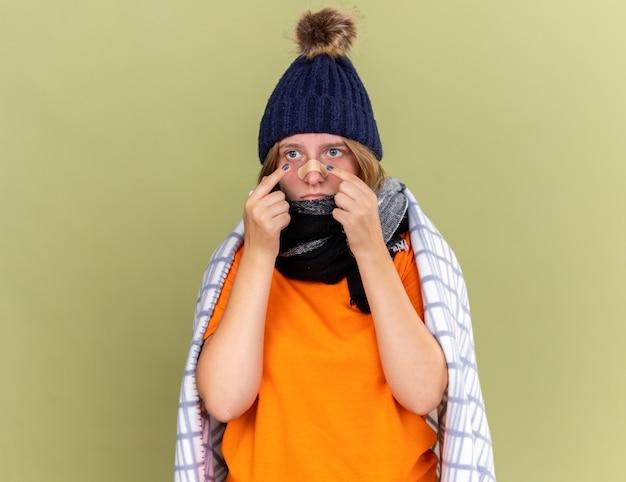 Giovane donna malsana con cappello caldo e sciarpa intorno al collo avvolta in una coperta che si sente male con una toppa attaccata al naso che sembra confusa e preoccupata in piedi sul muro verde