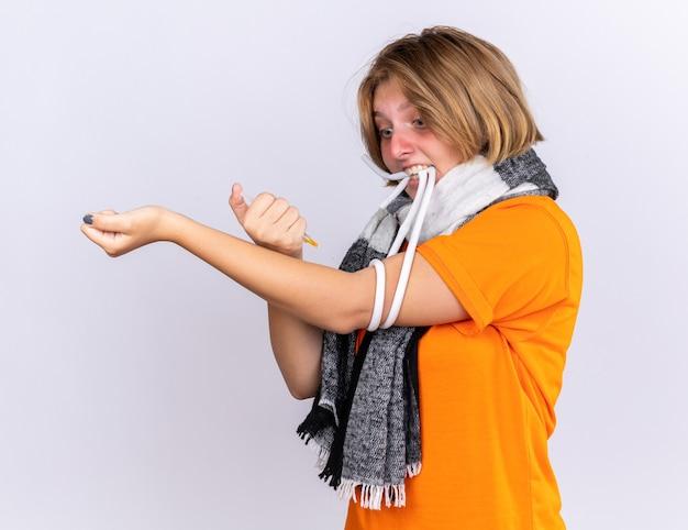그녀의 목 주위에 따뜻한 스카프로 건강에 해로운 젊은 여성은 감기와 독감으로 고통 받고 자신에게 주사를 맞고 걱정을하고 있습니다.