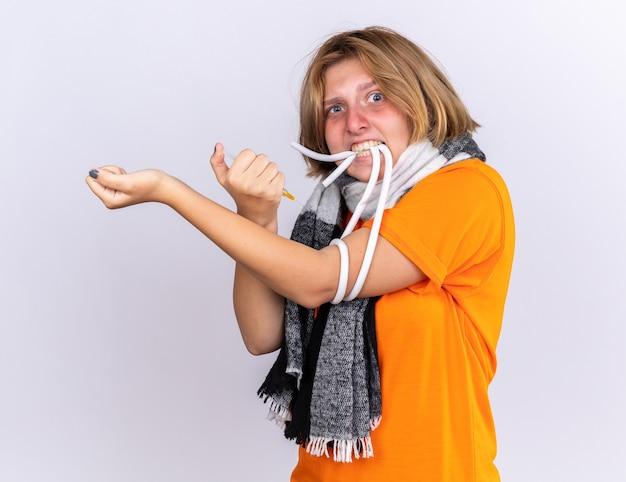 Giovane donna malsana con una sciarpa calda intorno al collo che si sente male soffre di raffreddore e influenza facendo un'iniezione a se stessa sembra spaventata
