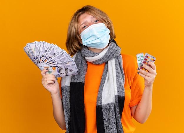 首の周りに暖かいスカーフを身に着けている不健康な若い女性は、ピルと現金を保持している保護フェイシャルマスクを身に着けている自信を持って見える