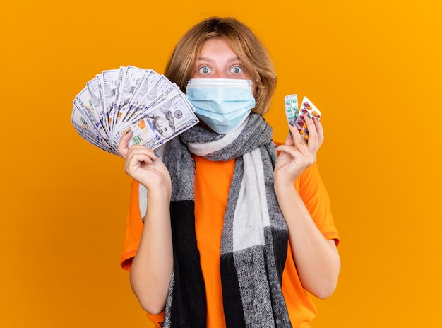 オレンジ色の壁の上に立って驚いて混乱しているように見える、薬と現金を保持する保護顔のマスクを身に着けた、首に暖かいスカーフを巻いた不健康な若い女性