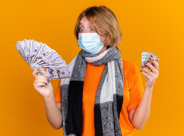 首の周りに暖かいスカーフを身に着けている不健康な若い女性は、ピルと現金を保持している保護フェイシャルマスクを身に着けて驚いて混乱しているように見えます