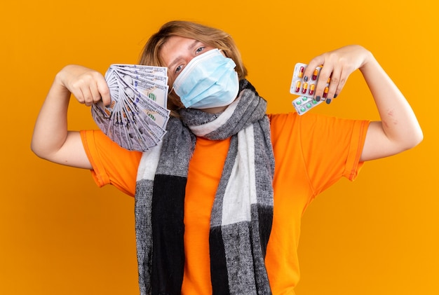 Unhealthy young woman with warm scarf around her neck wearing protective facial mask holding pills and cash looking confident