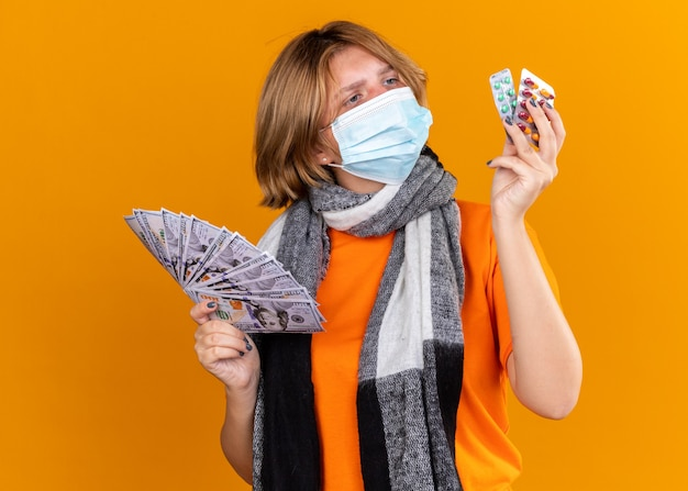 Unhealthy young woman with warm scarf around her neck wearing protective facial mask holding pills and cash looking confused