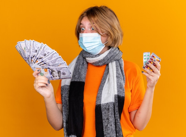 Unhealthy young woman with warm scarf around her neck wearing protective facial mask holding pills and cash looking surprised and confused