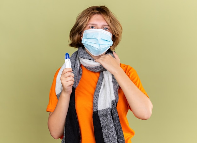 Unhealthy young woman with warm scarf around her neck wearing protective facial mask holding thermometer suffering from throat sore touching neck standing over green wall