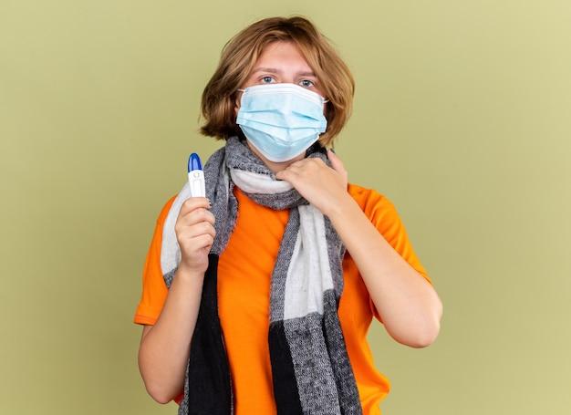 Нездоровая молодая женщина с теплым шарфом на шее в защитной маске для лица с термометром, страдающая от боли в горле, касающаяся шеи, стоящая над зеленой стеной