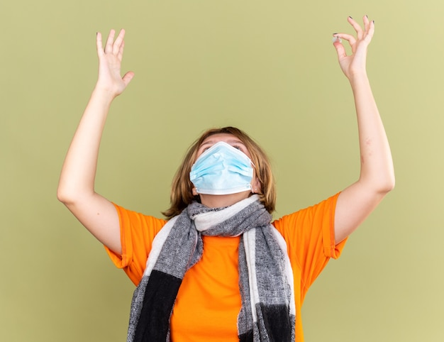 冷たいスカーフを首に巻いた不健康な若い女性が、風邪やインフルエンザに苦しんでいる保護用の顔面マスクを着て、緑の壁の上に立つ失望した表情で手を上げている