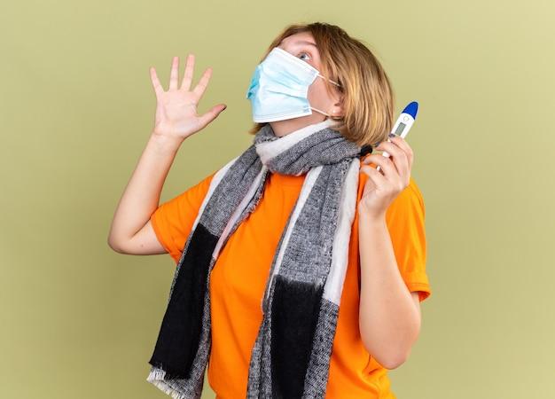Giovane donna malsana con una sciarpa calda intorno al collo che indossa una maschera facciale protettiva che soffre di raffreddore e influenza con termometro con febbre che sembra spaventata in piedi sul muro verde